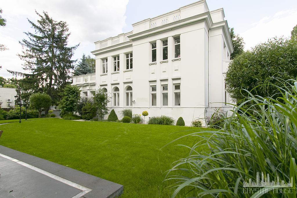 willa w stylu pałacowym i przystrzyżony trawnik przed nią