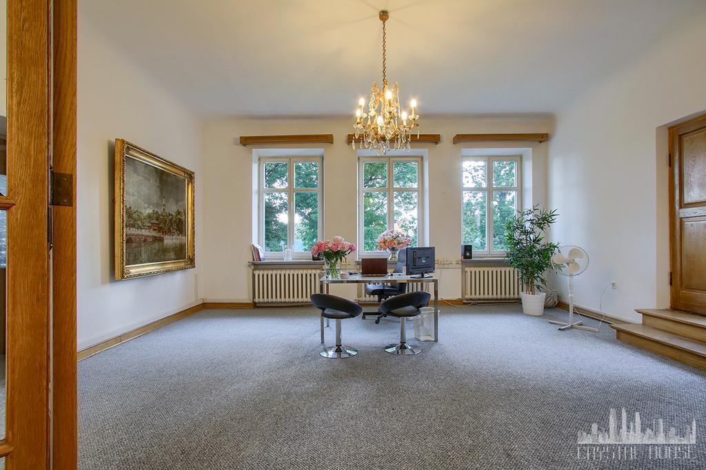 duże pomieszczenie biurowe z biurkiem i wykładziną