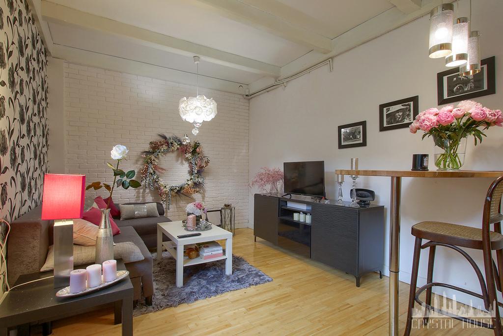 salon z tapetą, malowaną na biało cegłą i szarymi meblami