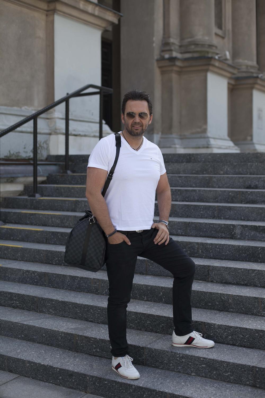 Mężczyzna z torbą Louis Vuitton na schodach