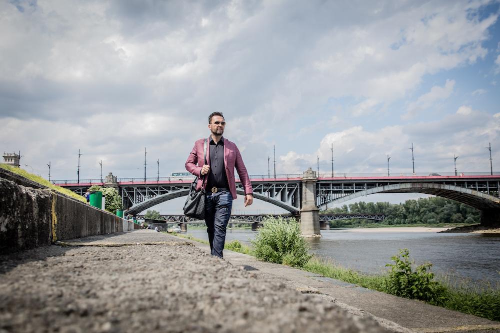 Mężczyzna z torbą Louis Vuitton na tle mostu
