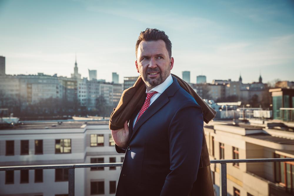Elegancki mężczyzna na tle panoramy Warszawy